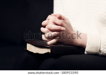 Woman folding hands over her holy bible and praying to God. - stock photo
