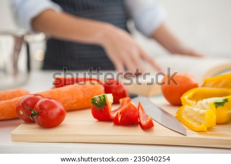 Woman following a recipe in book at home in the kitchen - stock photo