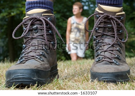 Woman following the hiker. Hiking boots in front.