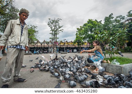 woman food to pigeons at chiangmai Gate , Chiangmai , Thailand on August 10 2014.