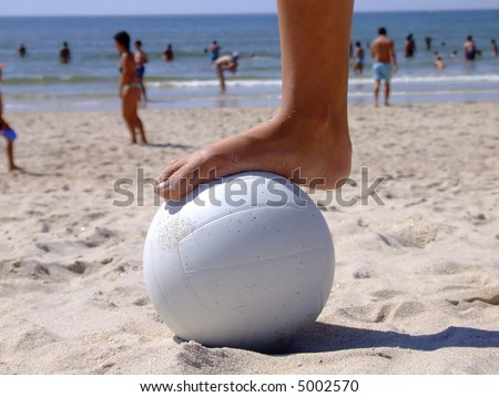 Woman foot on a volleyball on the sand