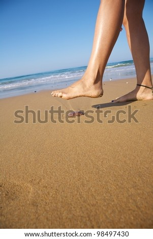 woman foot ready to push a medusa in a beach