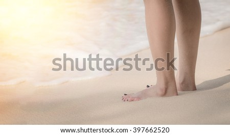 Woman foot resting on the sand by the sea, stood calmly in a holiday vacation in the summer. Light Flare.Waiting with loneliness