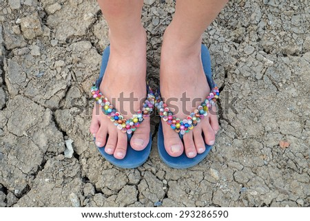 Woman foot with colorful slippers on crack soil background - stock photo