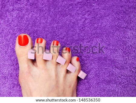 woman foot with spacers in pedicure treatment nail polishing - stock photo