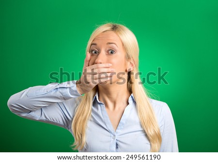 Woman forced to cover her mouth with hand isolated on green background. Fright scared face expression. Human emotion perception reaction. Freedom of speech violation concept. Gender inequality  - stock photo