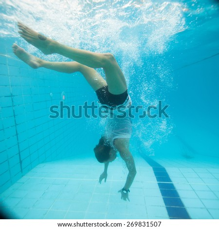 Woman freediving underwater in a pool