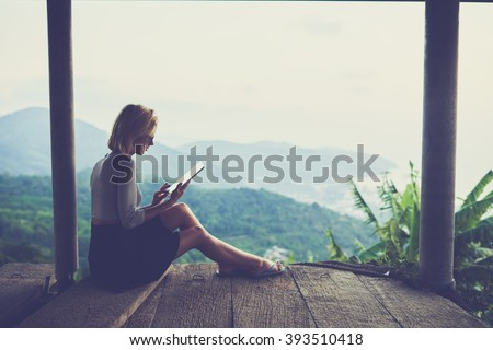 Woman freelancer is working on distance via portable digital tablet, while sitting against wonderful jungle scenery background with copy space for your advertising text message or promotional content - stock photo