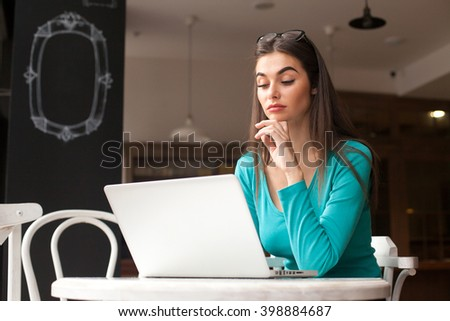 Woman-freelancer with black glasses is working with her grey laptop at the wood table and thinking about something