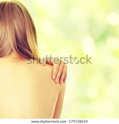 Woman from behind, naked body, pain concept,against abstract green background - stock photo