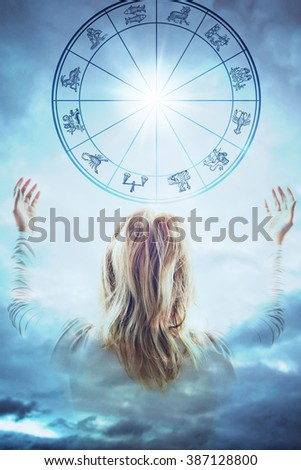 woman from behind with open arms in front of a sky with astrological chart