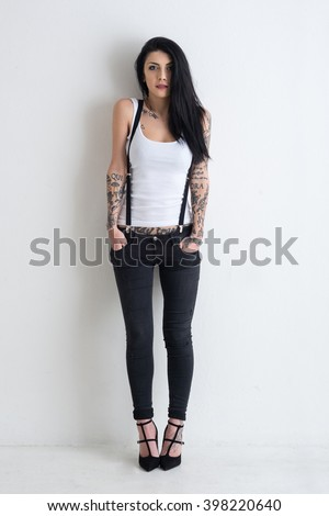 Woman full body portrait with tattoo against white wall background.