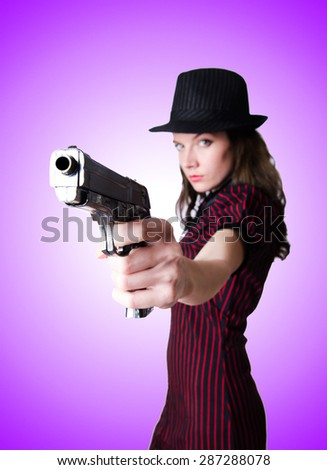Woman gangster with handgun against the gradient - stock photo
