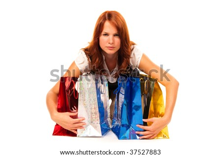 Woman gathering four gift bags, looking asquint. - stock photo