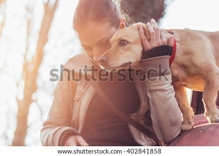 Woman gently hugging her pet dog - stock photo