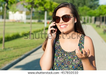 Woman gesturing and talking on phone outside in park in sunlight with copy text space - stock photo