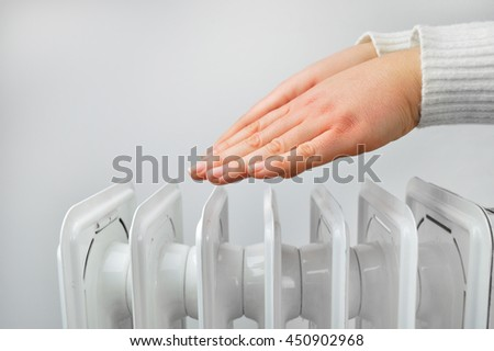 woman gettin warm up her hands over an electric radiator of heating at home