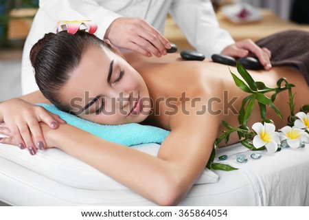 Woman getting a hot stone massage at spa salon - stock photo