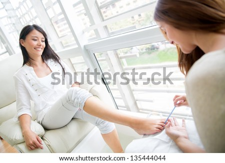 Woman getting a pedicure and relaxing at the beauty salon