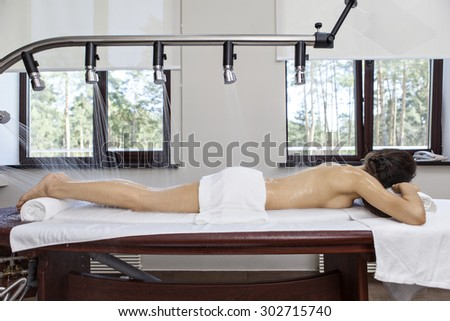 Woman getting a rain massage in the luxury spa salon - stock photo