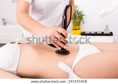 Woman getting anti cellulite and anti fat therapy in beauty salon