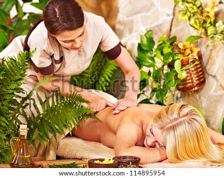 Woman getting back massage in beauty tropical spa. - stock photo