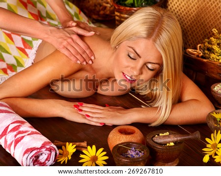 Woman getting back massage in tropical spa. - stock photo