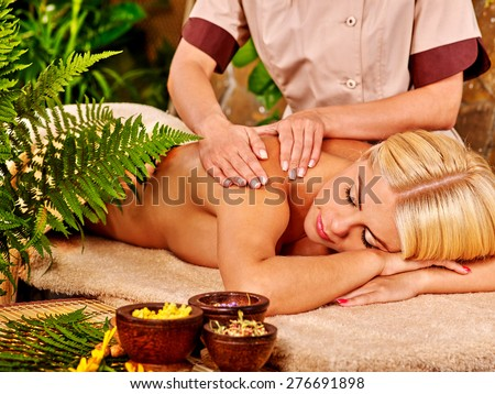 Woman getting back massage in tropical spa with green leaf. - stock photo