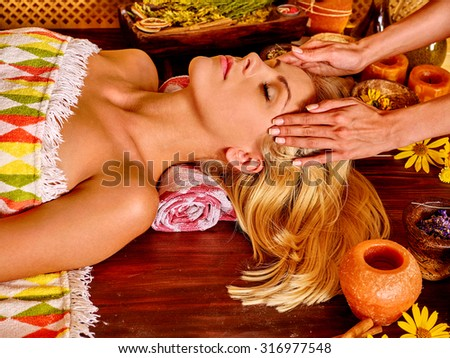 Woman getting facial massage in tropical spa.