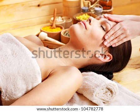 Woman getting facial  massage in wooden spa. - stock photo