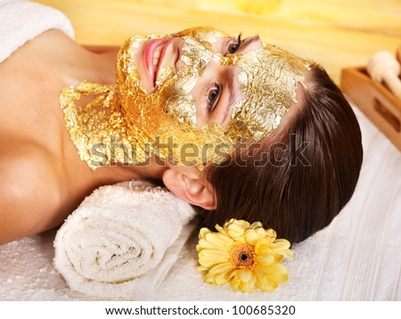 Woman getting gold facial mask. - stock photo