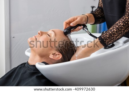 Woman Getting Hair Washed In Salon - stock photo