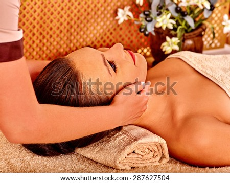 Woman getting head massage in tropical beauty spa. A lot of flower. - stock photo
