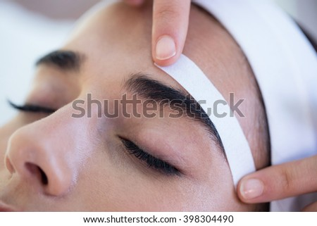 Woman getting her eyebrows shaped at spa - stock photo