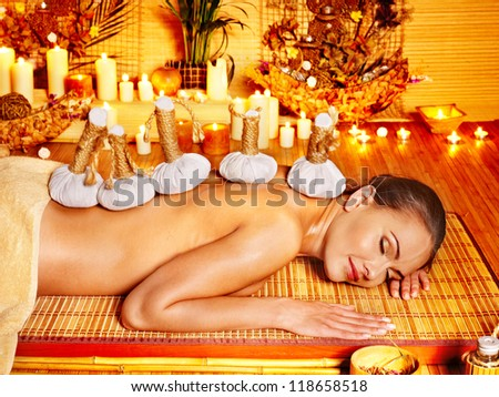 Woman getting herbal ball massage by candlelight in spa.