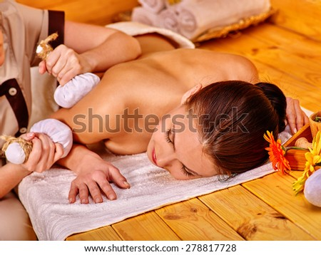 Woman getting herbal ball massage  in spa resort. One red flower.
