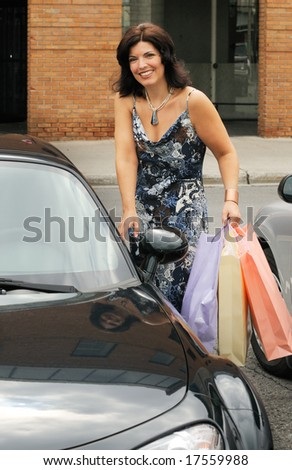 Woman Getting Into Her Car After A Shopping  Trip - stock photo