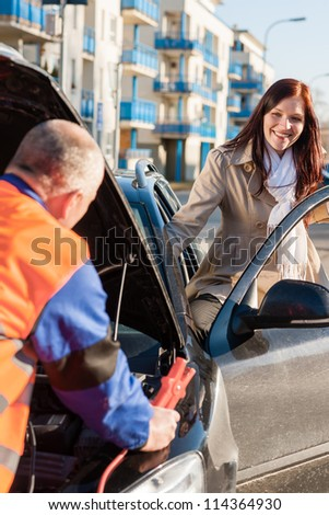 Woman getting into her car mechanic fixing with cables - stock photo