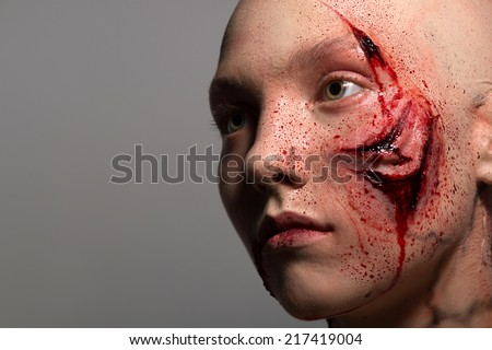Woman getting into the accident having a big terrible gash on her face isolated on grey background