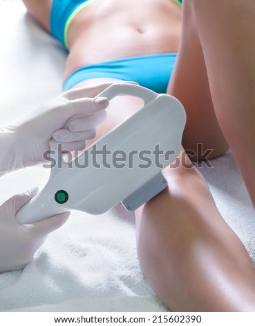Woman getting laser treatment in medical spa center, permanent hair removal concept - stock photo