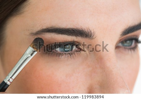Woman getting made up with eye shadow - stock photo