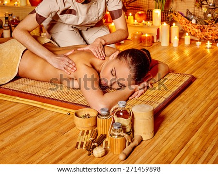 Woman getting  massage in spa. Bottle on foreground - stock photo
