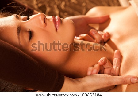 woman getting neck and face  massage in spa salon - stock photo