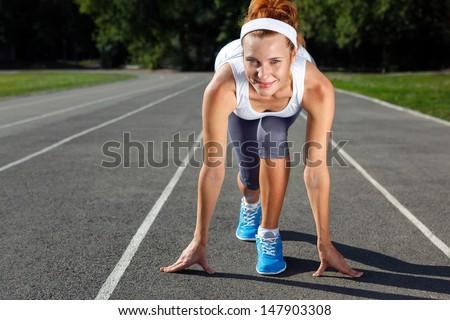 Woman getting ready to start on Stadium - summer outdoors training. - stock photo
