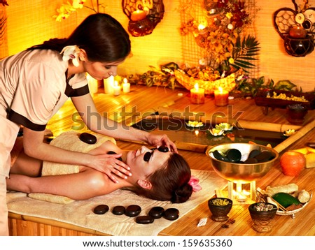 Woman getting stone therapy massage in bamboo spa. - stock photo
