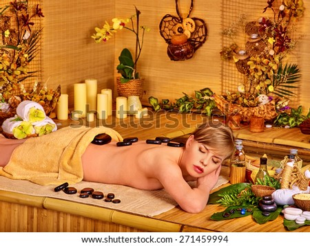 Woman getting stone therapy massage in bamboo spa. A lot of flower and candle. - stock photo