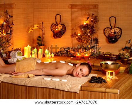 Woman getting stone therapy massage in bamboo spa.Luxury salon in oriental style - stock photo