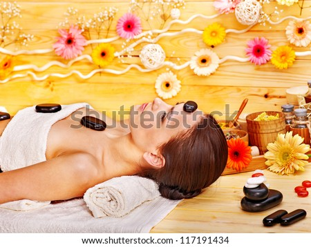 Woman getting stone therapy massage in wooden spa. - stock photo