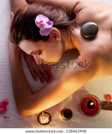 Woman getting stones spa procedures. - stock photo