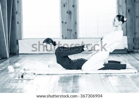 Woman getting thai stretching massage  - stock photo